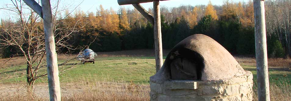 Photo of outdoor cob (earth) oven with an autumn backdrop