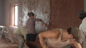 Photo of the fermata team hard at work applying natural plaster to a straw bale wall